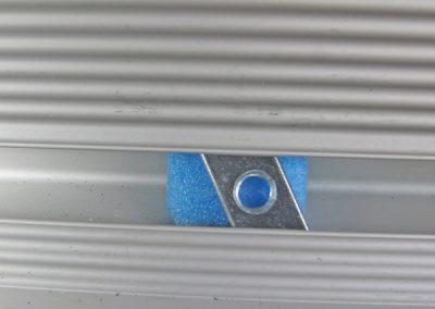 Trapezstein in Zurrschiene. Um den Stein besser montieren zu können wurde dahinter ein blaues Schaumstoffpad eingelegt.