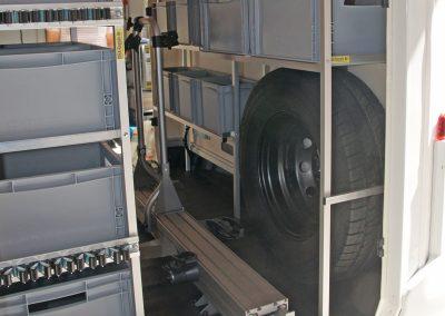 Boxenregal mit Gerätehaltern, gegenüber ein Reserveradüberbau