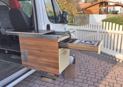 Oben aufgesetzt eine Tischplatte, darunter der Kocher eingebaut in einer Schublade