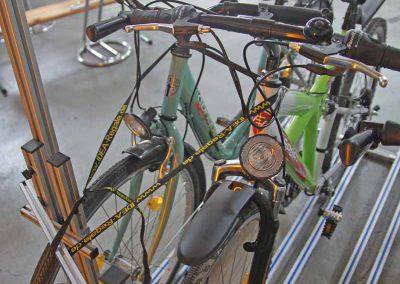 Pedi-Packer - die Radfixierung erfolgt am Lenkerkopf zur Stütze mit langen Spannriemen.